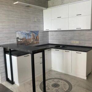 Белая кухня с барной стойкой и черной столешницей